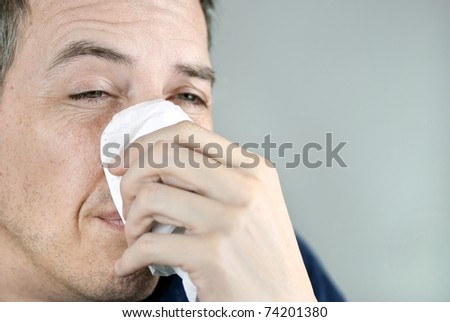 Close-up of a man holding a  tissue on his nose. - stock photo