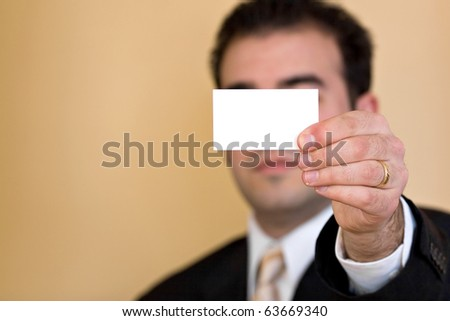 Close up of a man holding an empty business card up.  Plenty of copy space for your logo or design.  Shallow depth of field. - stock photo