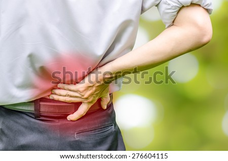close up of a  man holding his back in pain, monochrome photo with red as a symbol for the hardening - stock photo