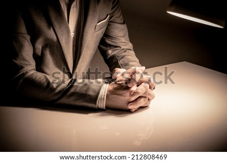 close up of a man in a suit with his hands clasped in front - stock photo