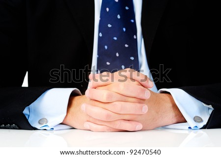 Close up of a man in a suit with his hands clasped in front of him - stock photo