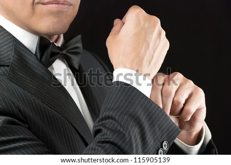 Close-up of a man in a tux fixing his cufflink. - stock photo