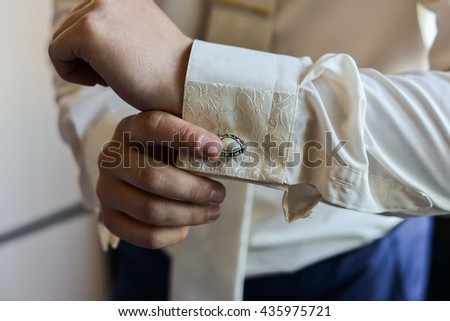 Close-up of a man in a tux fixing his cufflink. groom bow tie cufflinks - stock photo