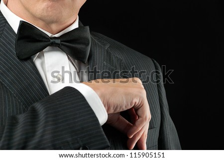 Close-up of a man in a tux tucking in his pocket square. - stock photo
