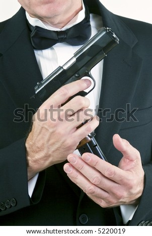 Close up of a man in formal attire, loading his automatic weapon taken agains a white background. - stock photo