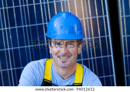 Close up of a Man in his forties overseeing a Solar Installation with Solar Panels behind him - stock photo