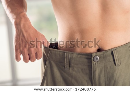 Close-up of a man in wide trousers losing weight - stock photo