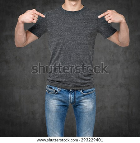 Close-up of a man pointing his fingers on a blank grey t-shirt. Dark concrete background. - stock photo
