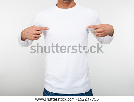 Close-up of a man pointing his fingers on a blank t-shirt - stock photo