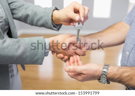 Close up of a man receiving a handshake and a key at the same time - stock photo