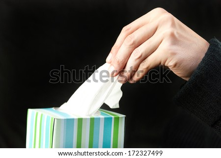 Close-up of a man's hand pulling a tissue out of the box. - stock photo