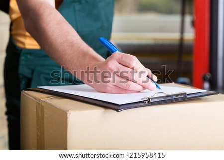 Close-up of a man's hand signing delivery document  - stock photo
