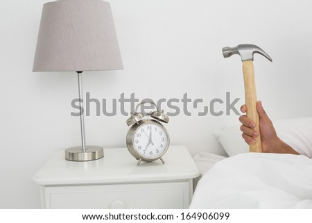 Close-up of a man's hand smashing alarm clock with hammer in bed at home - stock photo