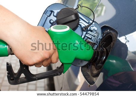 Close-up of a man's hand using a petrol pump to fill his car up with fuel - stock photo