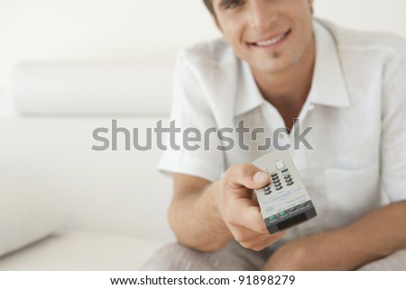 Close up of a man's hand using a tv remote control at home. - stock photo