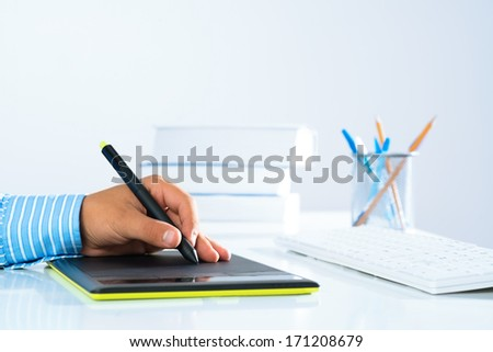 close-up of a man's hand with a pen stylus, drawing on a graphic tablet - stock photo
