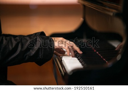 Close up of a man's hands playing a piano in church. - stock photo