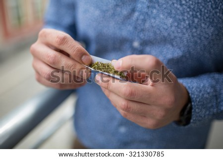 Close up of a man's hands rolling up a marijuana joint - stock photo