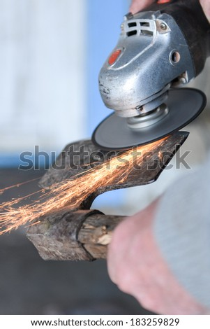 Close up of a man sharpen an ax using electric grinder. Sparks while grinding iron. Selective focus - stock photo