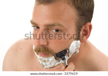 Close-up of a man shaving off his thick beard with a metal razor. Isolated on white background.