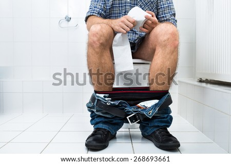 Close-up Of A Man Sitting On Commode Holding Tissue Paper Roll - stock photo