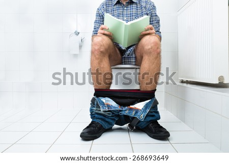 Close-up Of A Man Sitting On Commode Reading Book - stock photo