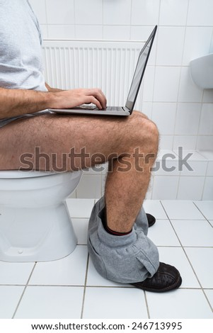 Close-up Of A Man Sitting On Commode Using Laptop - stock photo