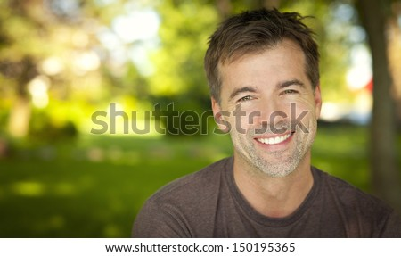 Close-up of a man smiling outside - stock photo