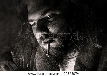 close up of a man smoking a cigarette with dramatic lighting - stock photo