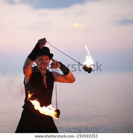 Close up of a man spinning fire poi - stock photo