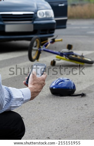 Close-up of a man using his mobile phone to call for help on road - stock photo