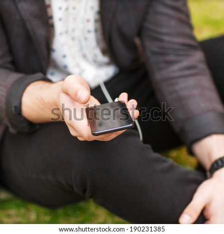Close up of a man using mp3 player - stock photo