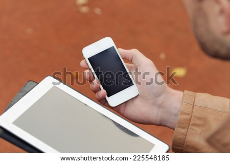 close up of a man using tablet and phone device on autumn background, technology concept - stock photo