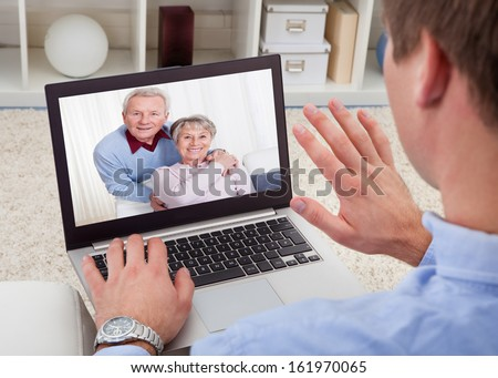 Close-up Of A Man Video Chatting On Laptop With His Parents - stock photo