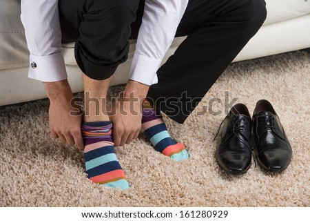Close up of a man wearing colorful sock under classical business suite. Idea of being different  - stock photo