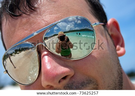 Close up of a man wearing reflective sunglasses in a tropical beach with reflection of the woman photographer in the lens. Shallow depth of field. - stock photo