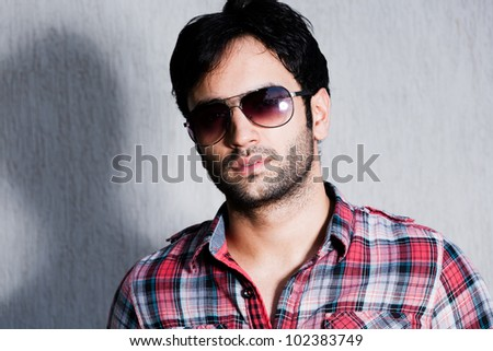 close up of a man wearing sunglasses against a grey wall, close up of a happy man wearing sunglasses