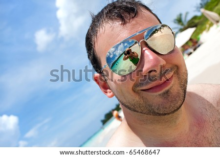 Close up of a man wearing sunglasses in a tropical beach with reflection of the female photographer in the lens. Shallow depth of field. - stock photo