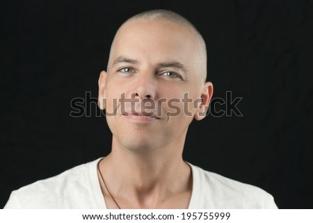 Close-up of a man with a newly shaved head looking to camera. - stock photo