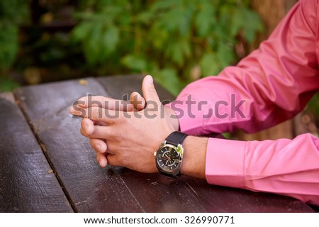 Close up of a man with his hands clasped in front of him. - stock photo