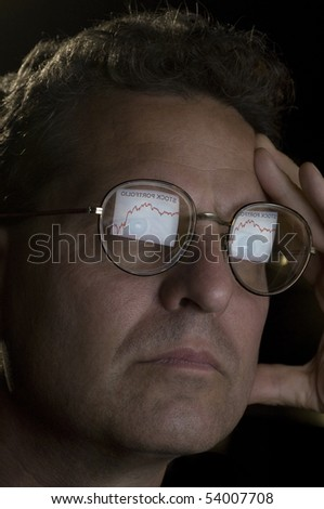 Close-up of a man with the reflection of his computer screen in his glasses showing a declining stock portfolio - stock photo