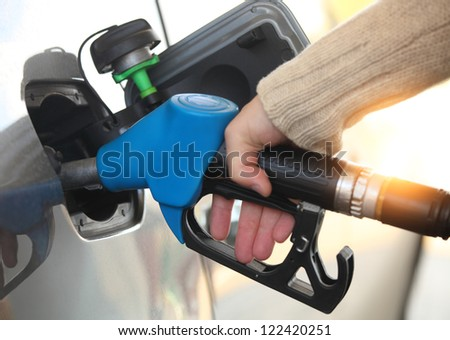 Close up of a mans hand refilling the car with a gas pump - stock photo
