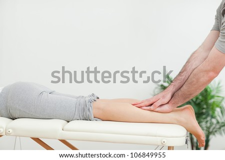 Close up of a masseur massaging the calves of a woman in a room