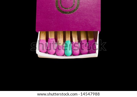 Close up of a matches box showing matches in a row with one match of a different color. Black background. - stock photo