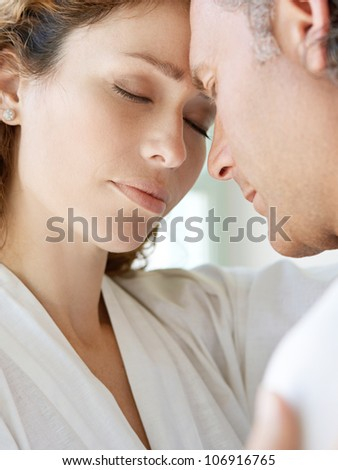Close up of a  mature couple hugging at home, with their foreheads together.