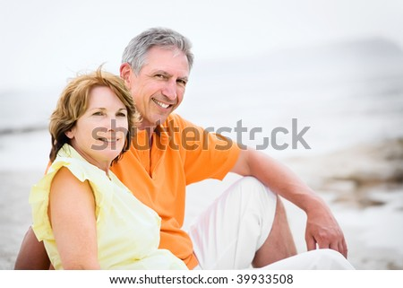Close-up of a mature couple relaxing on the beach - stock photo
