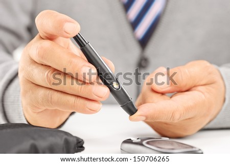 Close up of a mature diabetic patient measuring sugar level in blood using glucometer - stock photo