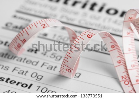 Close up of a measure tape on a nutrition fact sheet - stock photo