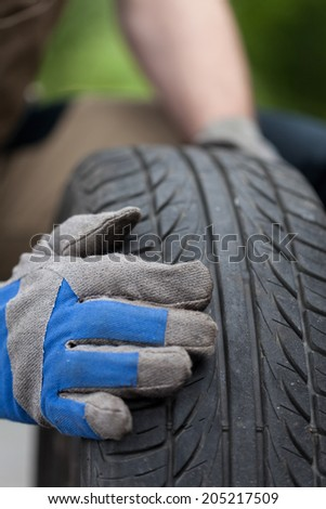 Close-up of a mechanic hands and car tire - stock photo