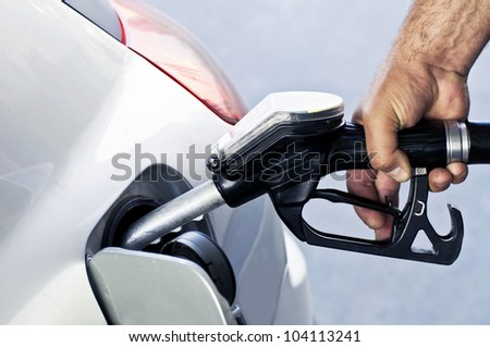 Close-up of a mens hand refilling the car with a gas